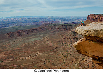Female Hiker Looks Down Over Grand View in Island in the Sky...
