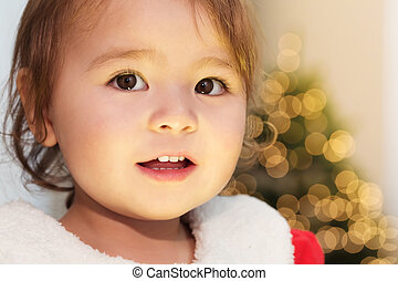 Little girl smiling in front of her Christmas tree - Happy...