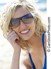 Beautiful Young Blond Woman in Sunglasses Smiling At The Beach