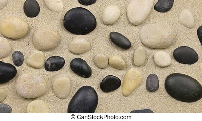 Approximation of black and white stones on the sand, a top view