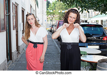 Two Women Walking on Sidewalk Together - Confident Brunette...