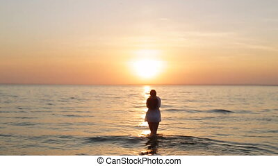 a girl walks into the sea at sunset slow motion - a girl...