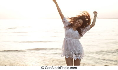 beauty happy smiling woman at sea at sunset slow motion