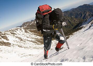 Mountain climber with ice axe on snow slap.
