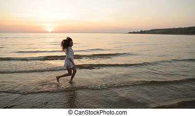 Young woman running on sea coast at sunset slow motion