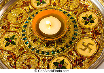 Diya lamp on a decorated golden plate - Traditional diwali...