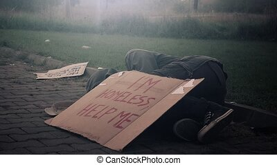 Homeless beggar sleeping on the street, adult man begging...