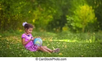 teen girl sitting on  green  grass playing studying Globe happy color