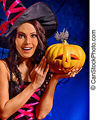 Witch holding pumpkin - Happy witch holding orange carving...