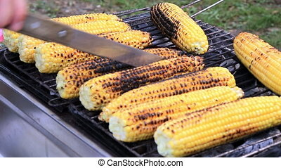 Baked corn on the grill - Man which revolves corn on the...