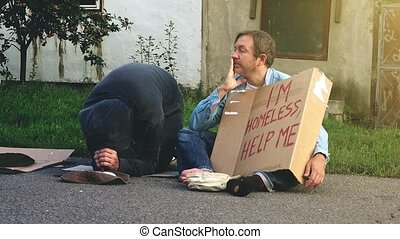 Taking money from homeless people - Man taking money from...