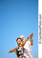 Mature couple on blue sky background - Bright lifestyle...