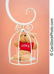 Bear doll in white bird cage