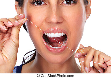 Woman teeth with dental floss.