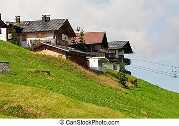 Alpine chalets on hill. Summer time - Alpine chalets on a...
