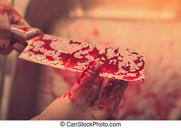 Hand hold bloody knife in a steel shell for halloween (...