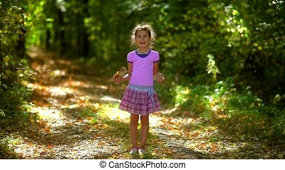 Portrait teen girl throws jumping yellow leaves of autumn...