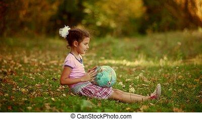 teen  girl brunette sitting on green grass playing studying Glob