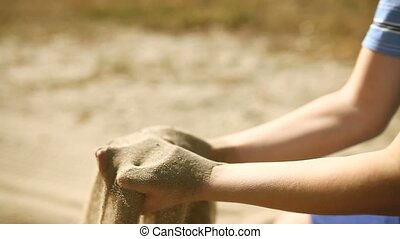 Teen big hand boy pours sand symbol time desert - Teen big...