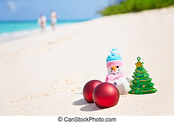 Snowman on the sandy sea beach. Holiday Christmas concept...