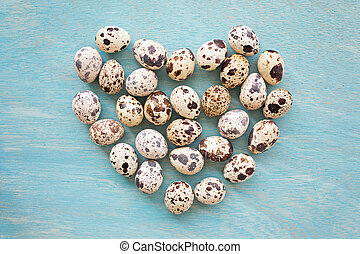 quail eggs on a blue wooden background in shape of heart, top view
