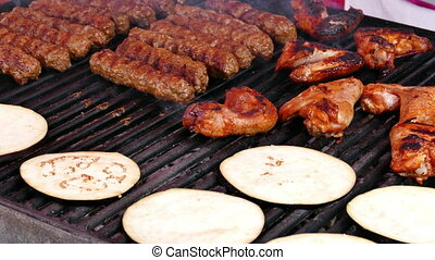 Romanian sausages (mici) chicken wings and eggplant slices,...
