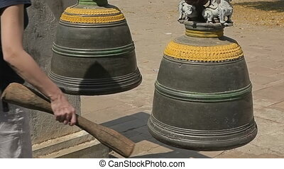 Prayer bell - Tourist strike a prayer bell at The Ananda...