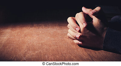 Hands Of Praying - Praying hands of young man on a wooden...