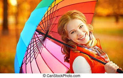 happy woman with rainbow multicolored umbrella under rain in...