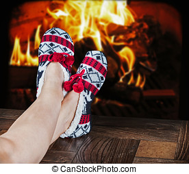 Christmas female slippers on the background of a burning...