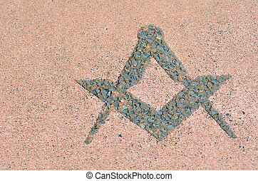 Freemasonry symbol made from stones on the ground