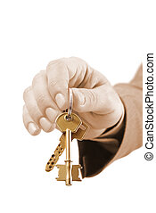 Male real estate executive hand holding two keys. - Close-up...