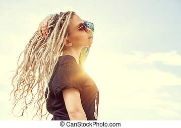breathe - Modern girl with long blonde dreadlocks standing...
