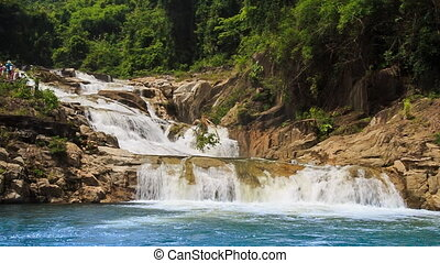 waterfall flows among rocks falls into lake in tropical park...