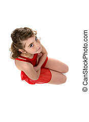 young girl in red leotard kneeling and looking serious