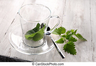 Preparing fresh nettle tea with the green leaves of the...