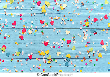 Blue wood background with scattered party confetti - Blue...