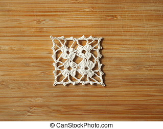 Crocheted snow flake on a wooden background.