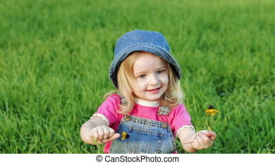 Child on lawn with flower