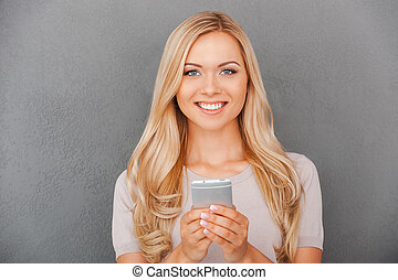 Beauty with smart phone Smiling young businesswoman holding...