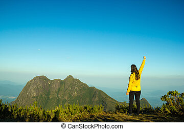 Woman Celebrating Sucess on the Cliff - Woman celebrating...
