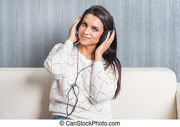 young woman listening music  with headphones in room at home on the sofa look camera