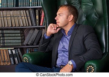 The man, calm and confident businessman sitting in a chair, library