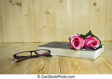 book - Old books with roses flower and vintage glasses on a...