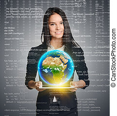 Smiling woman holding Earth globe over tablet on computer code background