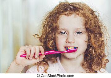 Portrait of the little girl brushing her teeth