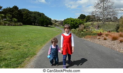 Two sisters holding hands and walking together in the park