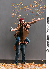 Autumn fun. Full length of handsome young man piggybacking...