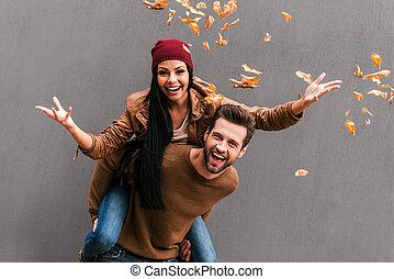 Carefree fun. Handsome young man piggybacking his girlfriend...