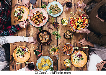 Enjoying dinner together. Top view of four people having...